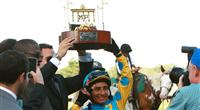 Jockey Rafael Bejarano celebrates in the winners circle after his victory on Paynter in the 2012 Haskell.